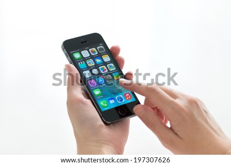 KIEV, UKRAINE - MAY 21, 2014: Person holding a brand new black Apple iPhone 5S, the most advanced smartphone in part of the iPhone line. Developed by Apple inc. and was released on September 20, 2013. - stock photo
