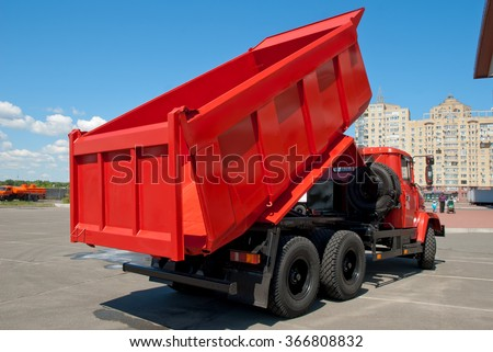 Kiev, Ukraine - May 26,  2009. Red dump truck with the body lifted for unloading. - stock photo