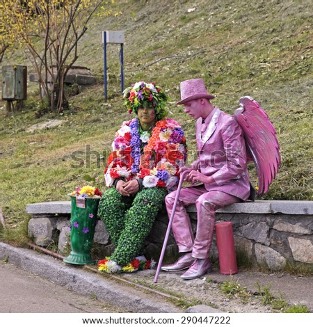 KIEV, UKRAINE - MAY 01, 2015: Two unidentified busking mimes in costumes relax at park in Kiev, Ukraine. Living statues are the entertainment for the tourists. - stock photo