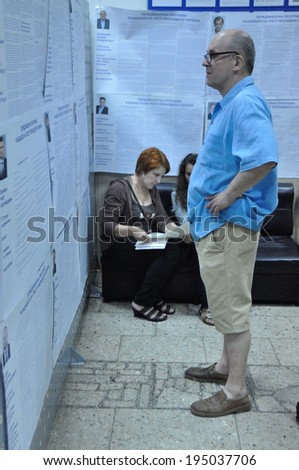 KIEV, UKRAINE -Â?Â? 25 MAY 2014: Unknown people study biographes of candidates on the president and local election on 25 May 2014 in Kiev, Ukraine.