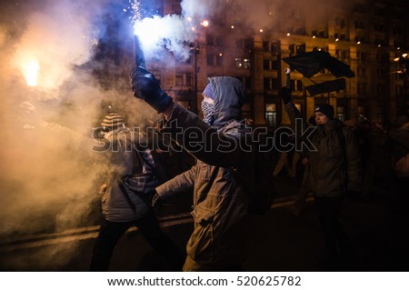 KIEV, UKRAINE - Nov 21, 2016: Men burn flares during a rally held by activists of nationalist groups and their supporters who mark the anniversary of 2014 Ukrainian pro-European Union mass protests
