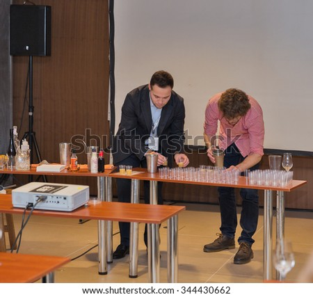 KIEV, UKRAINE - NOVEMBER 21, 2015: Unrecognized presenters prepare cocktail samples with Single Malt Scotch Whisky for tasting at 1st Whisky Dram Festival in Parkovy Exhibition Center.