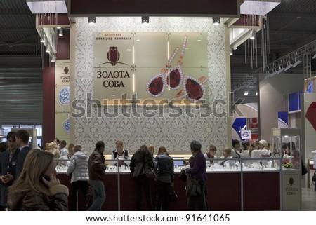 KIEV, UKRAINE - NOVEMBER 17: Visitors visit Kyiv Gold Owl Jewelry company booth during Autumn Jeweler Expo exhibition at KyivExpoPlaza Exhibition Center on November 17, 2011 in Kiev, Ukraine. - stock photo