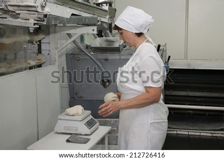 KIEV, UKRAINE - on August 21, 2014: the worker of the Kiev grain plant, moves ready dough to the container