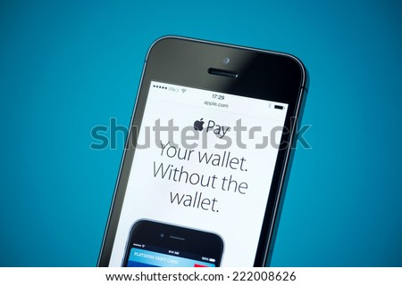 Kiev, Ukraine - September 24, 2014: Close-up shot of brand new Apple iPhone 5S showing apple.com website with news announce of Apple Pay service. - stock photo