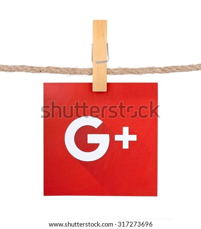 KIEV, UKRAINE - SEPTEMBER 16, 2015: Popular social media Google plus hanging on the clothesline isolated on white background.Google plus which provides the ability to communicate via the Internet. - stock photo