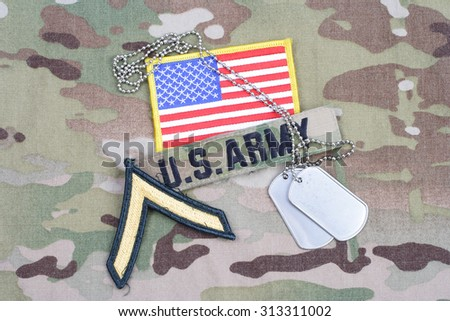 KIEV, UKRAINE - September 5, 2015. US ARMY Private rank patch,  flag patch, with dog tag on camouflage uniform