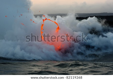 Kilauea volcano lava flow spitting into the air and ocean. Hawaii Volcanoes National Park.