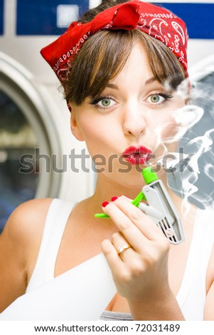 Killer Cleaning Lady Kills Germs In Style While Puffing On The End Of A Smoking Spray Bottle In A Funny And Humorous House Clean Concept - stock photo
