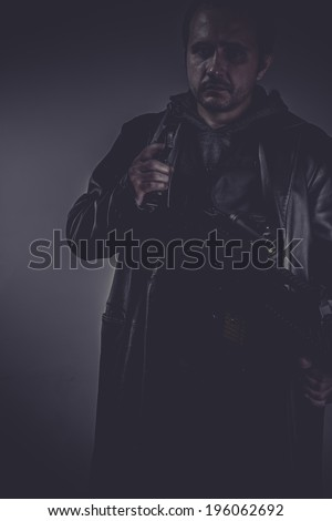 Killer, portrait of stylish man with long leather jacket, gun armed - stock photo