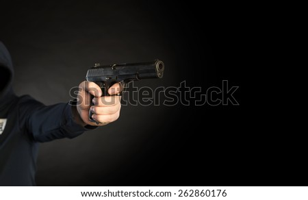 killer shooting a gun  isolated on  black background - stock photo