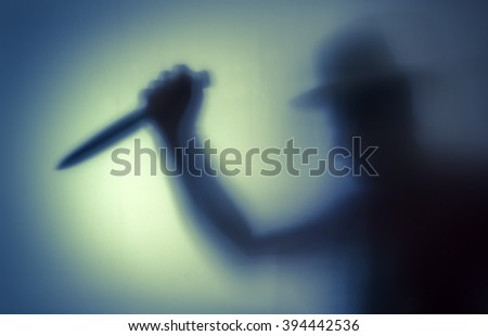 Killer with a knife in her hand. Shadowy figure behind glass  - stock photo