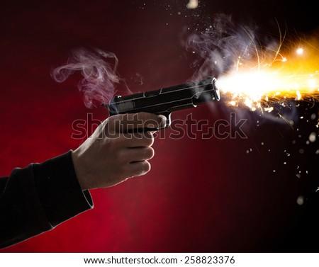 Killer with gun close-up on dark background - stock photo