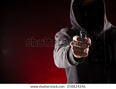 Killer with gun close-up on dark background - stock photo