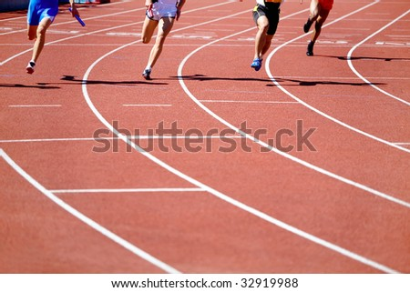 Kind of running legs of the men in relay race competition  in movement - stock photo