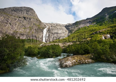 Kind on glacier Briksdayl, with the mountain river following from it, Norway,