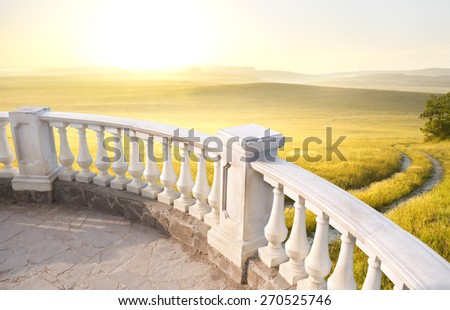 Kind on mountains meadow from a stone balcony - stock photo