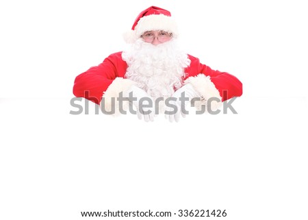 Kind Santa Claus looking out from behind the blank sign isolated on white background with copy space