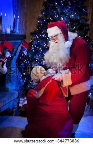 Kind Santa Claus Taking a Present From the Big Red Bag in the Christmas Night