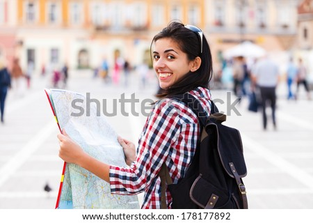 Kind tourist with backpack smiling and examining map. - stock photo