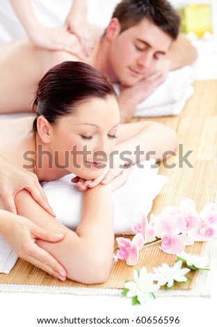 Kind young couple receiving a back massage in a spa center - stock photo