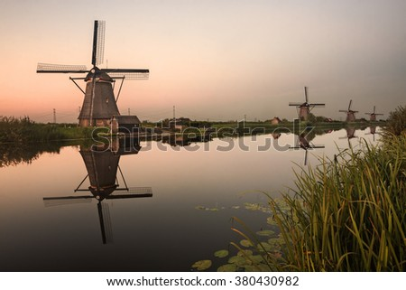 Kinderdijk, Holland: traditional windmills ad sunset with reflection on the canal