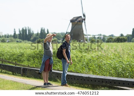 KINDERDIJK, NETHERLANDS - JULY 6, 2015: Two young tourists says one of the typical windmills of that region of the Netherlands.