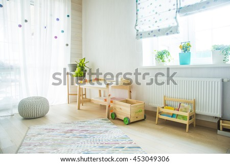 Kindergarten apartment with easel chair and table for painting. children's room and furniture and natural green flowers on white windowsill