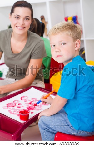 kindergarten boy and female teacher in classroom