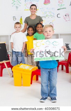 kindergarten boy holding his paint in front of classmates - stock photo