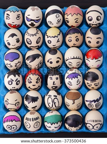 Kindergarten Children's craft of faces painted on eggs - stock photo