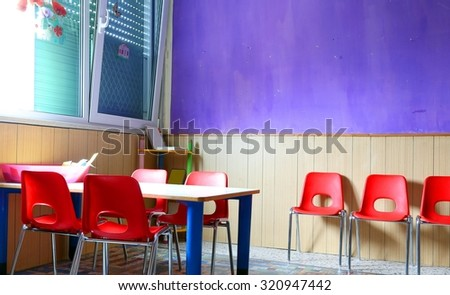 kindergarten classroom with desks and red chairs - stock photo
