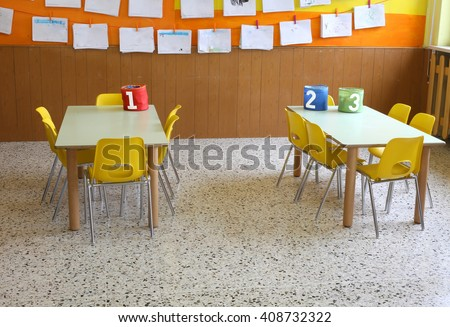 kindergarten classroom with the yellow chairs and many children's drawings on the walls - stock photo