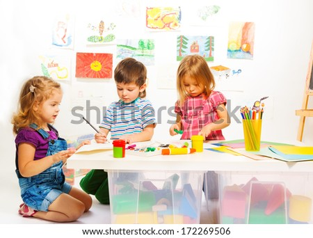 Kindergarten kids by the table gluing and painting on creative art class - stock photo