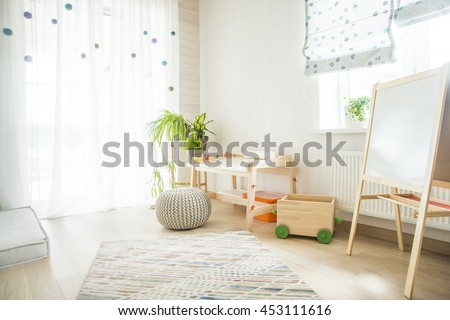 Kindergarten room with easel chair and table for painting. children's room and furniture and natural green flowers on white windowsill - stock photo