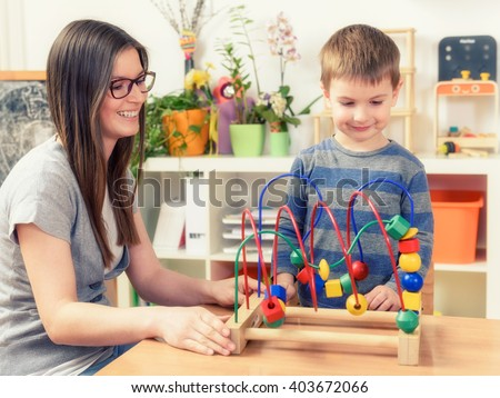 Kindergarten Teacher and  Boy Playing With Bead roller coaster - stock photo