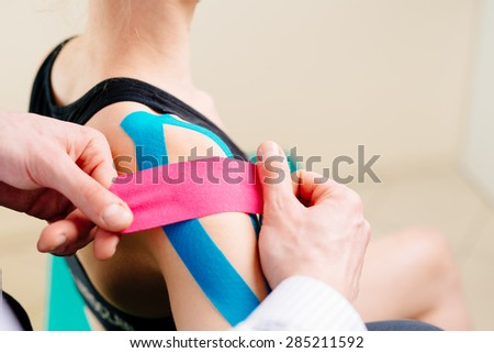 Kinesiotaping. Physical therapist applying tape to patient shoulder - stock photo