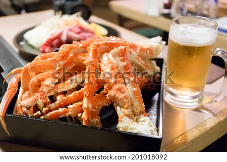 king crab legs and a glass of beer - stock photo