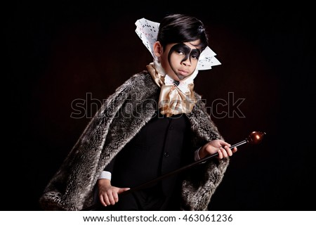King of Hearts.  Young, mixed race boy wearing a suit with a large collar made of playing cards, thick furry cape, black heart shaped face make-up and holding a scepter.