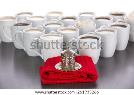King of the coffee concept with a small cup of Turkish coffee in a traditional metal covered cup standing on a red cloth in front of a triangle of full white ceramic cups of black and latte coffee - stock photo