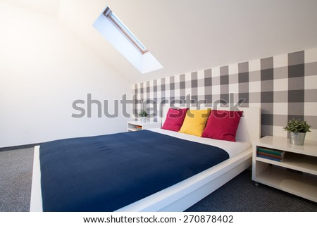 King size bed with colorful sheet in new bedroom - stock photo