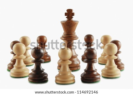 King surrounded by chess pawns - stock photo