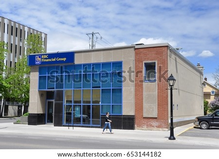Kingston, Ontario, Canada - May 28, 2017: Woman walks fast in front of  Royal Bank of Canada ( RBC ) Financial Group in Princess Street, Kingston.