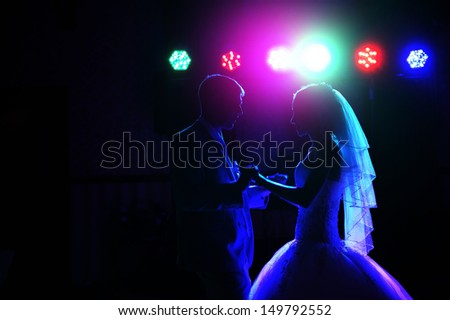 Kiss and dance young bride and groom in dark banqueting hall - stock photo