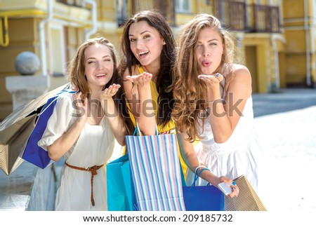 Kiss from three girlfriends. Three girls holding shopping bags and walk around the shops. Smiling girls having fun together - stock photo