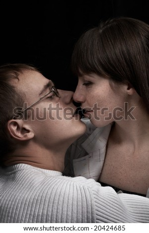 kiss loving couple isolated on black background