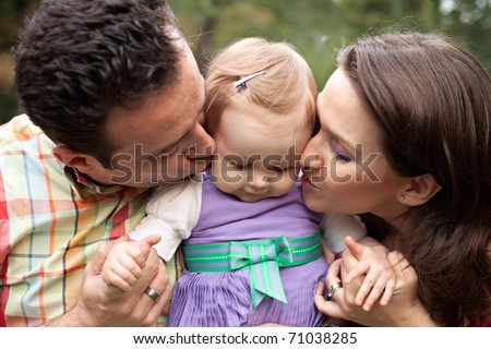 Kiss of love - happy parents with their cute baby girl - stock photo