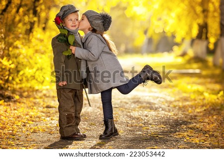 Kiss the girl and the boy's donated a rose at the meeting in the autumn park - stock photo