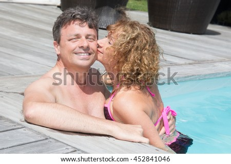 Kissing and charming couple having fun in swimming-pool - stock photo