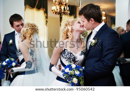 Kissing bride and groom in interior wedding palace - stock photo
